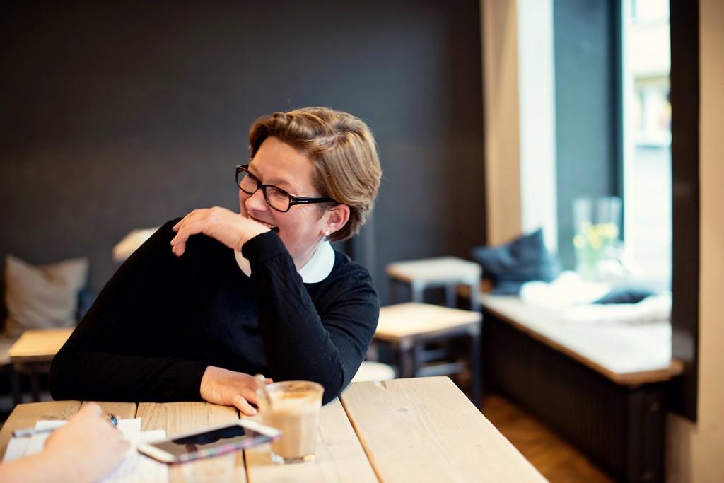 Lachend sitzt sie in ihrem Café und plaudert mit ihren Gästen - Foto bei Leni Moretti Photography